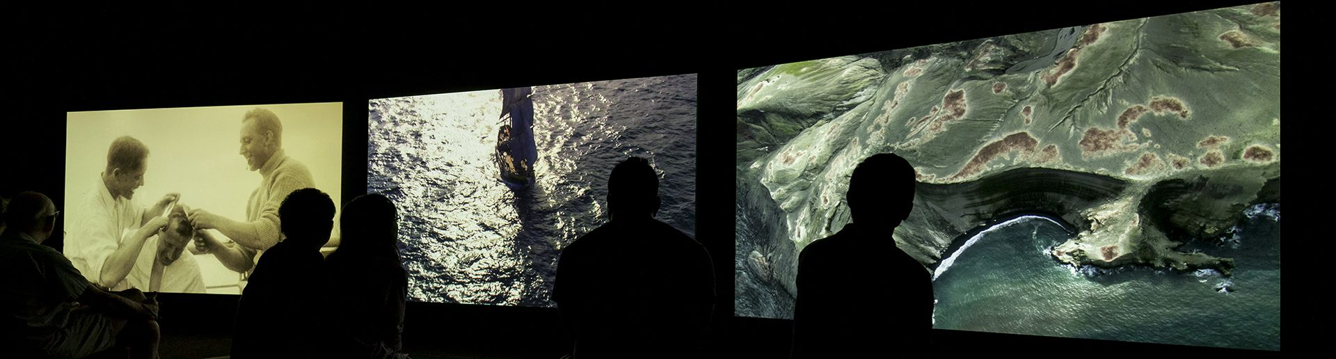 Viewers watch a three-screen video installation with scenes of water