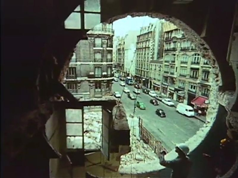 Looking out onto a street scene through a large cut hole in the side of a buliding