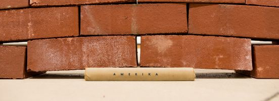 Red bricks stacked on top of a book whose spine reads Amerika