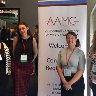 Four women stand next to a conference banner