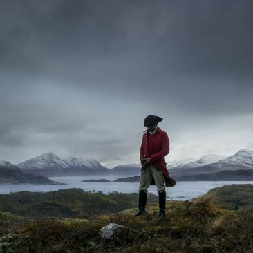 A man in a dark hat and red coat stands amidst a rocky field with water, mountains, and dark cloudy skies behind him.