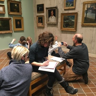 College students take notes studying paintings in a museum