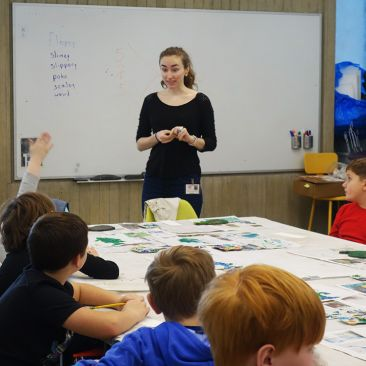 A young woman teaches in a classroom with young children at a table