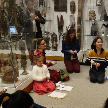A young woman describes objects in a museum gallery to visitors