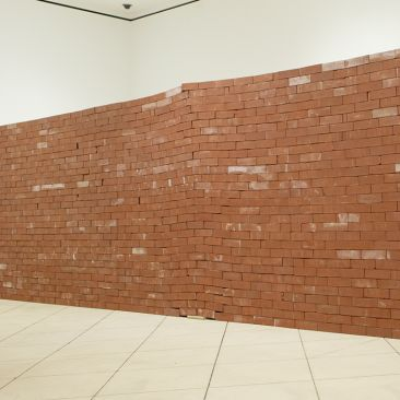 A portion of a red brick wall constructed in a museum gallery