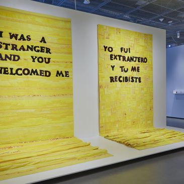 "Installation view of two large yellow quilts with black texts that read ""I was a stranger and you welcomed me"" and ""Yo fui extranjero y tu me recibiste"" hang upright on a white wall"