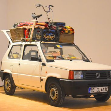A white Volkswagen hatchback is filled with objects inside and packed on the top