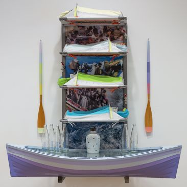 A colorful wall sculpture including a small canoe, oars, water bottles, and expanded hanging shelves