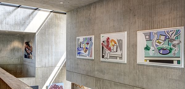 Colorful abstract paintings hang on concrete walls and shafts of light come from above into the museum lobby